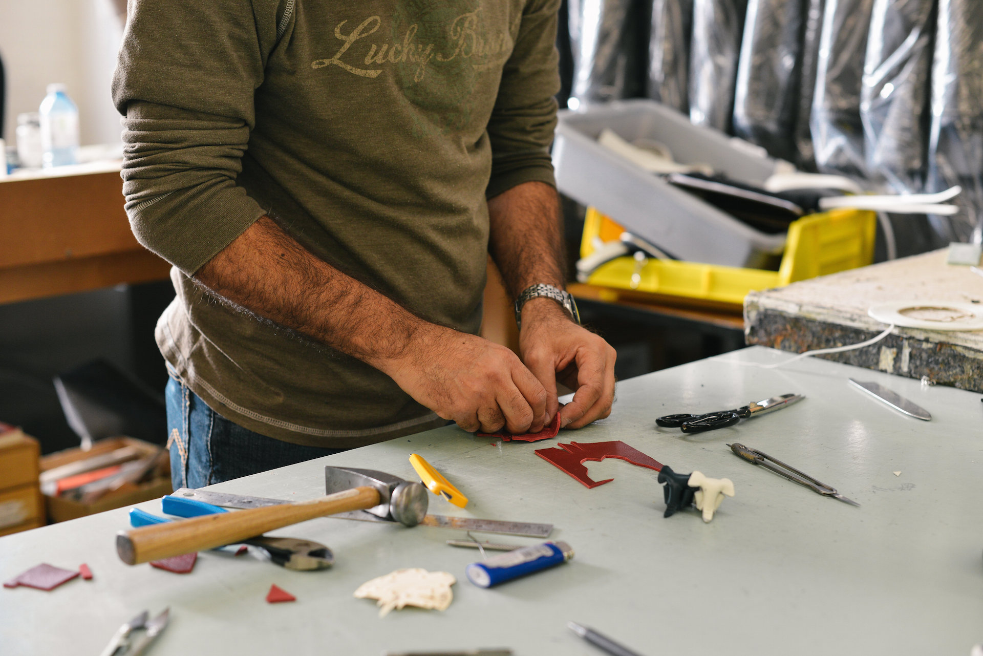 Man hands over a workspace crafting. Tools lie on the counter space next to him.