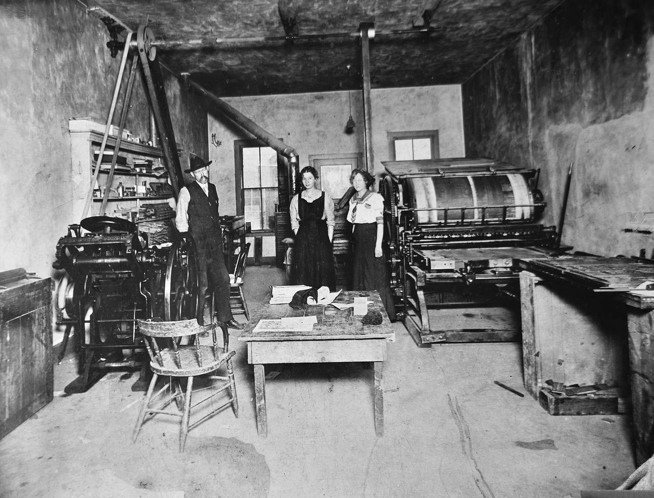 Two women and man stand in old printing press in Mancos.
