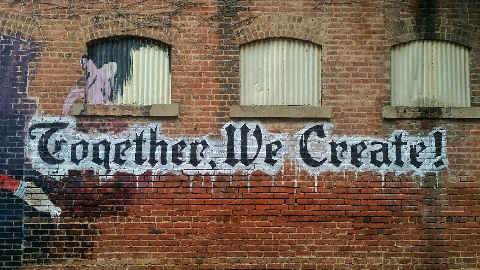 Painted on a brick wall reads together we create