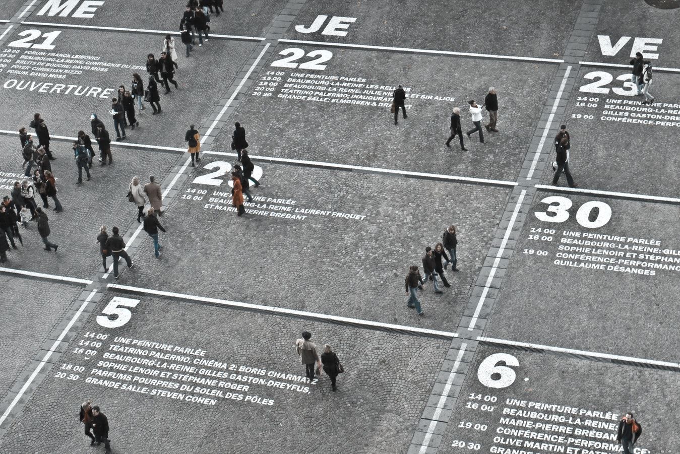 Aerial shot of people walking across a street that looks like a calendar