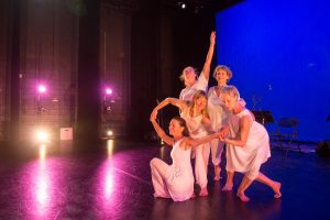 Purple and blue background with a group of dancers on stage performing